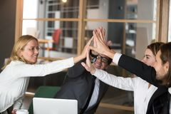Happy business team giving high-five together promising engageme. Happy business team giving high five promising engagement and loyalty, partners group joining Stock Images