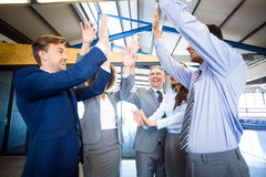 Happy business team high fiving Royalty Free Stock Image
