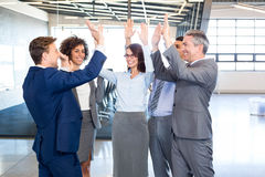 Happy business team high fiving Stock Photo