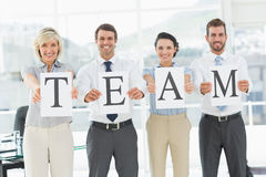 Happy business team holding papers indicating team Royalty Free Stock Photography