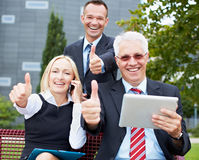 Happy business team holding thumbs Stock Photo