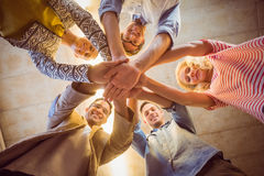 Happy business team joining their hands. In the office Royalty Free Stock Photos