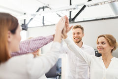 Happy business team making high five at office Stock Photography