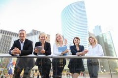 Happy business team members talking outside in  . Satisfied business team members speaking outdoors in  . Concept of biz partners enjoying successful result Royalty Free Stock Image