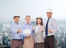 Happy business team in office showing thumbs up. Business, architecture and office concept - happy team of architects in office showing thumbs up Stock Photo
