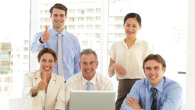 Happy business team posing in front of laptop stock footage