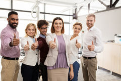 Happy business team showing thumbs up at office Royalty Free Stock Image