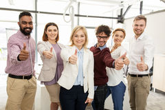 Happy business team showing thumbs up at office Stock Photos