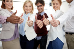 Happy business team showing thumbs up at office Royalty Free Stock Images