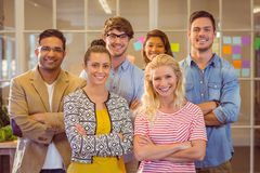 Happy business team smiling at camera with arms crossed Royalty Free Stock Image