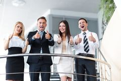 Business team standing on the terrace and shows thumb up. Royalty Free Stock Images