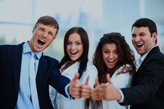 Happy business team with thumbs up in the office. Happy business team with thumbs up in the office Stock Images