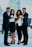 Happy business team with thumbs up in the office. Happy business team with thumbs up in the office Stock Photos