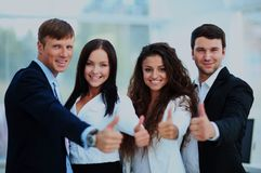 Happy business team with thumbs up in the office. Happy business team with thumbs up in the office Stock Photography