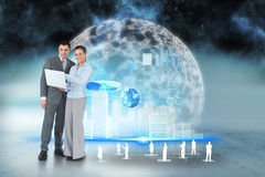 Happy business team using laptop with interface and human representations Stock Image