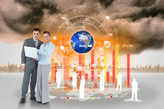 Happy business team using laptop with map and human representations Royalty Free Stock Photo