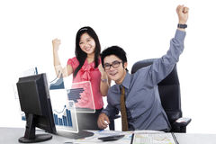 Happy business team with virtual growth chart. Picture of happy business team raising hands while looking at the camera with virtual growth chart on the computer Royalty Free Stock Images