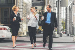 Happy business team walking in city Stock Photo