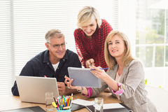 Happy business team working over a tablet Royalty Free Stock Photos