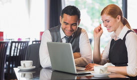 Happy business team working together in a cafe. With laptop Stock Images