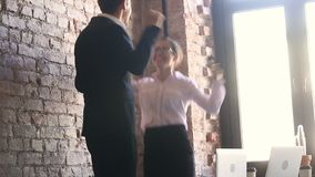 Happy business winners celebrating success jumping dancing together in office