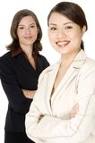 Happy Business Woman. A smiling asian businesswoman (in focus) stands in front of her western colleague stock images