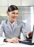Happy business woman. Smiling in office with laptop stock photography