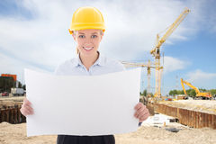 Happy business woman architect in yellow builder helmet holding Stock Photos