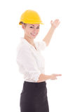 Happy business woman architect in yellow builder helmet pointing. At something isolated on white background Stock Photos