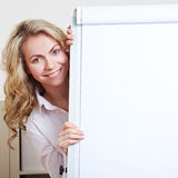 Happy business woman behind. Happy blonde business woman hiding behind a flipchart Royalty Free Stock Images