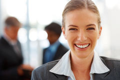 Happy business woman with colleagues at the back Royalty Free Stock Photos