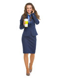 Happy business woman with cup of hot beverage talking cell phone Stock Photos