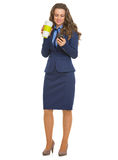 Happy business woman with cup of hot beverage writing sms Royalty Free Stock Photo