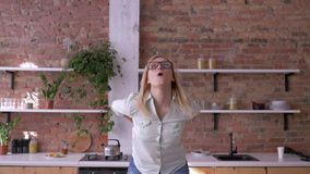 Happy business woman dancing and throwing paper documents in the kitchen, good start to new working day stock video