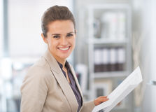 Happy business woman with documents in office Stock Photo