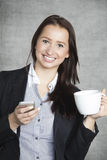 Happy business woman drinking coffee and writing SMS Royalty Free Stock Photos