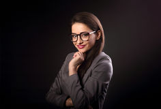 Happy business woman in eyeglasses looking on dark black backgro Royalty Free Stock Photography