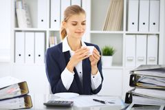 Happy business woman or female accountant having some minutes for coffee and pleasure at working place.  royalty free stock photo