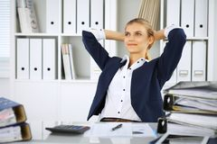 Happy business woman or female accountant having some minutes for coffee and pleasure at working place.  stock photos