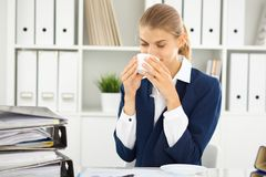 Happy business woman or female accountant having some minutes for coffee and pleasure at working place.  stock images