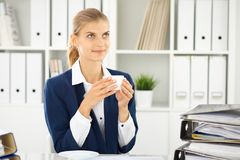 Happy business woman or female accountant having some minutes for coffee and pleasure at working place.  stock image