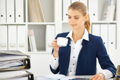 Happy business woman or female accountant having some minutes for coffee and pleasure at working place.  stock photography