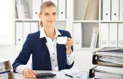 Happy business woman or female accountant having some minutes for coffee and pleasure at working place.  royalty free stock photography