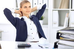 Happy business woman or female accountant having some minutes for coffee and pleasure at working place Royalty Free Stock Images
