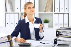 Happy business woman or female accountant having some minutes for coffee and pleasure at working place Royalty Free Stock Photography