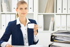 Happy business woman or female accountant having some minutes for coffee and pleasure at working place.  royalty free stock images