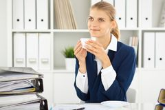Happy business woman or female accountant having some minutes for coffee and pleasure at working place.  royalty free stock image