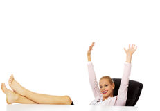 Happy business woman with hands up holding legs on the desk Stock Image