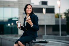 Happy business woman have lunch outdoor. Happy business woman in suit have lunch outdoor. Modern building, financial center, cityscape. Female businessperson in Stock Photo