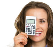 Happy business woman holding calculator in front of face Royalty Free Stock Photography